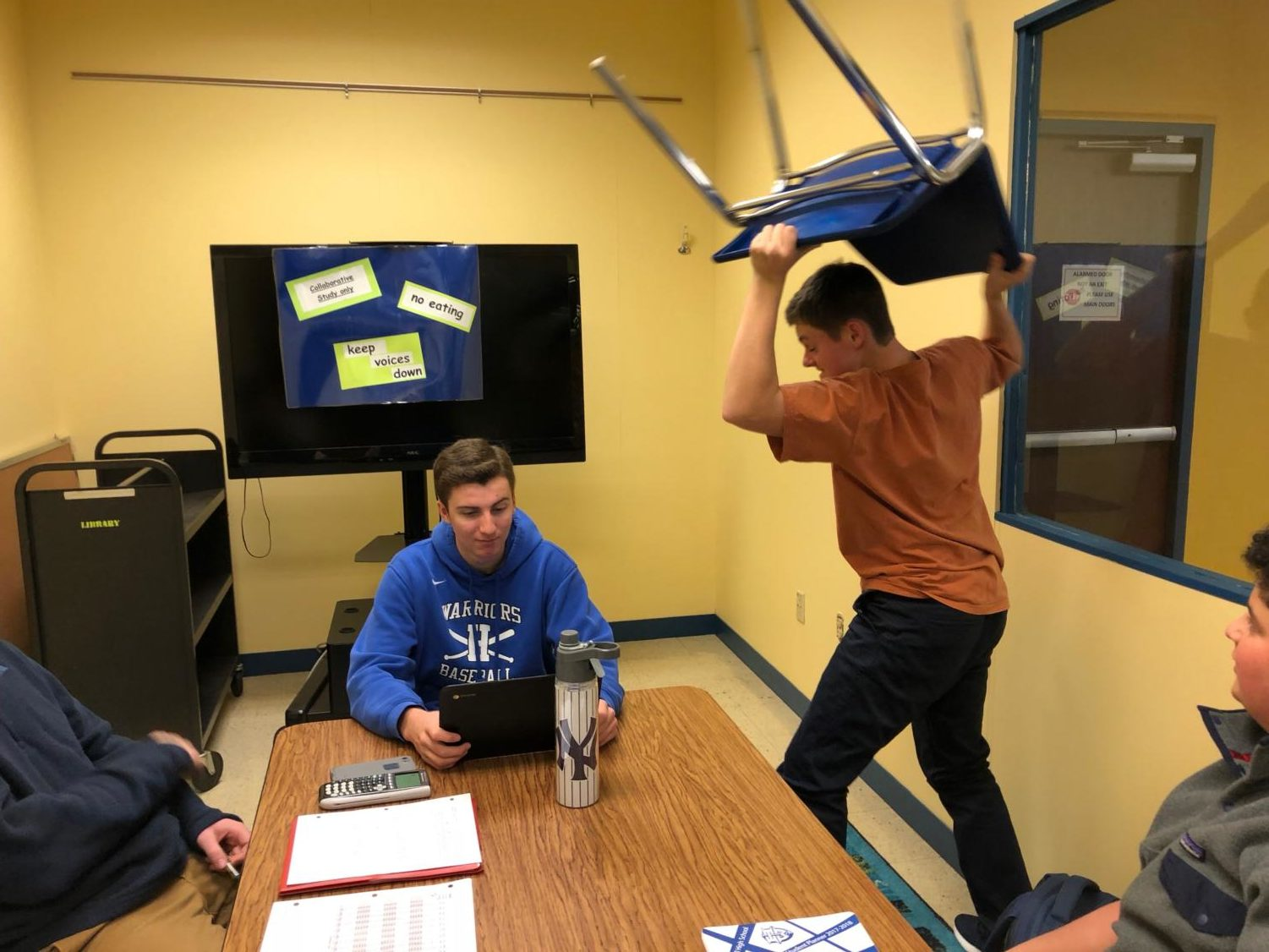 Student throws chair as a result of frustration with library policies.