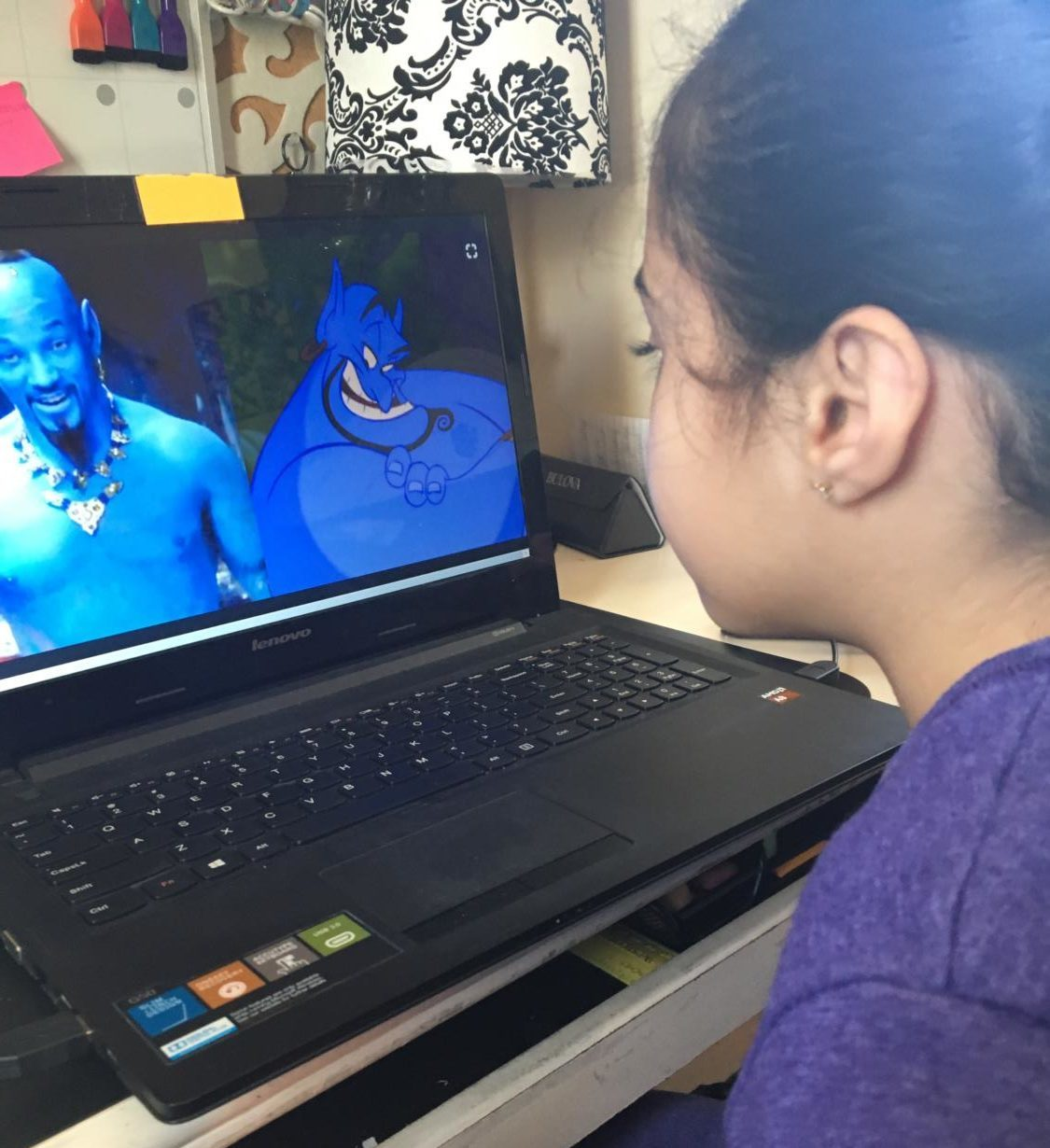 A child comparing photos of the classic animated Genie and the new live action Genie.