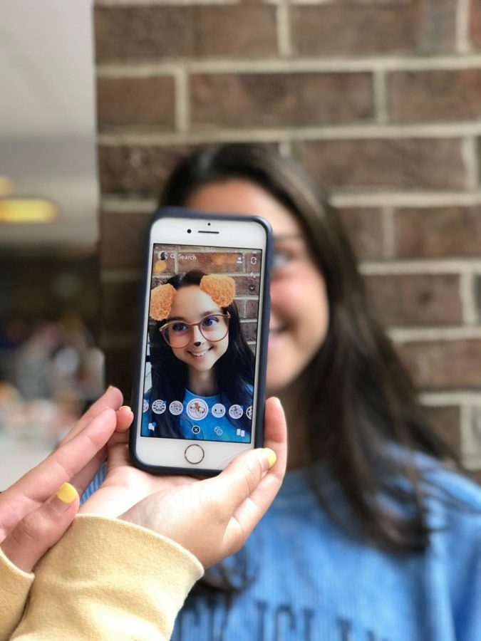 Sami Farber is using her cell phone to send silly pictures to her friends via Snapchat
