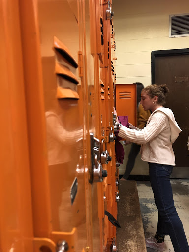 A student is pictured gathering her belongings at her locker after a long day of school and activities.