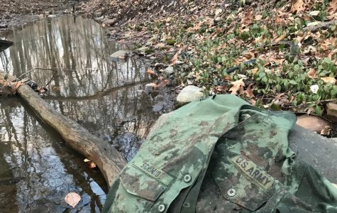 An old, mud-spattered, U.S. Army uniform rests on a rock in the forest.