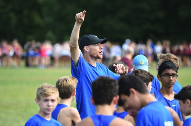 "Picture by Thomas Robinson  ""Coach Billing giving his motivational pre meet speech as the athletes get ready to run"""