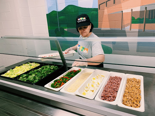 Pictured here is one of the lady's hired on the cafeteria staff at hall high school preparing the salad for lunch. She places a variety of healthy options that students can choose to put on their salads.