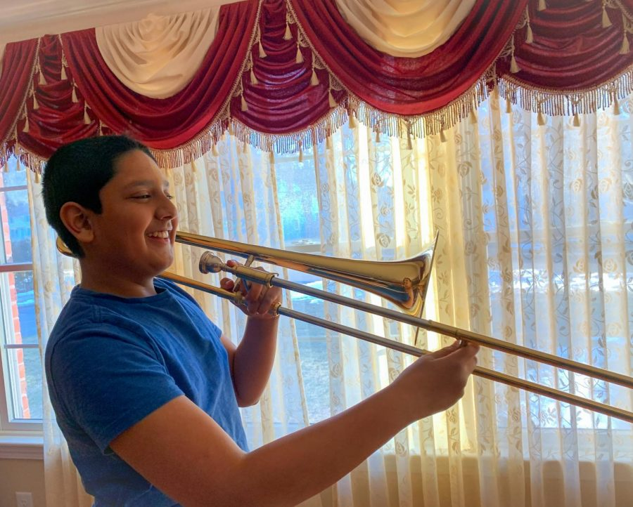 A Smith elementary school student enjoys time spent with his family as he plays the trombone in front of them on Sunday March 7th.