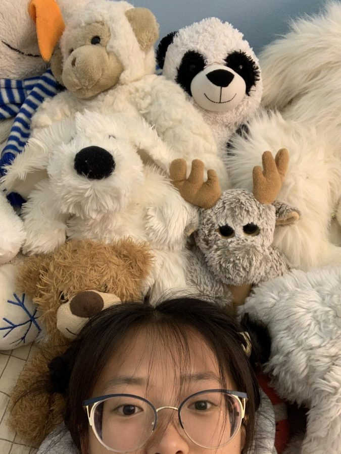 Surrounded by 13 stuffed animals that sleeps on a bed.