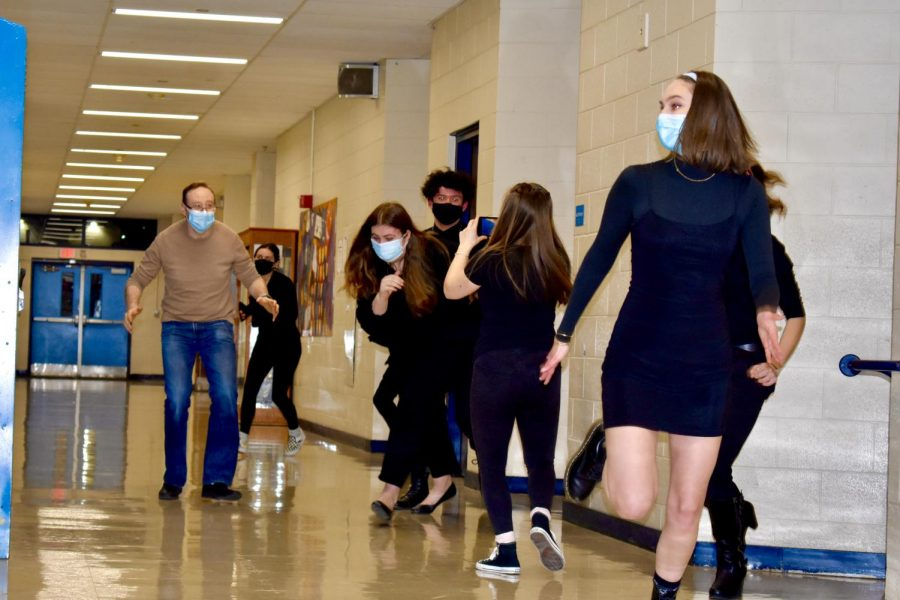 """Brett Boles, the Choraliers director, pretends to run after the """"chickens"""" (Grace Furia, Mauricio Vega Estades, and Delaney Fox, left to right) in the song """"Ain't Nobody Here But Us Chickens,"""" while senior Choralier Grace Maynard films for a scene of the PNJ production in a hallway at Hall High School, West Hartford, CT. (Taken March 1, 2021)"""