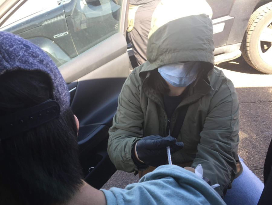 In a drive-through site, the nurse is administering the vaccine.